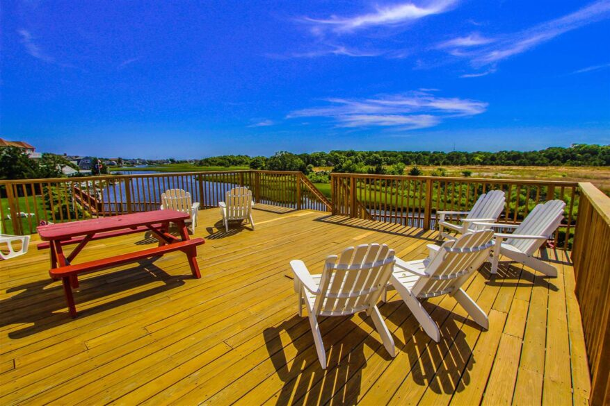 Deck with white chairs and red picnic table